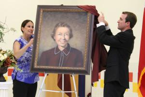 Smith Principal Jona Boitmann and Assistant Principal Brent Bellman unveil a portrait of Leta Horn Smith.