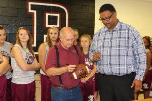 Former Princeton head football coaches Jackie Hendricks and Stacey Dillard sign a football for Camp iHope.