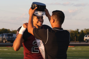 Princeton senior George Flores is bestowed the Homecoming King crown by 2014 winner Zac Torres before the start of the Sept. 18 game against Crandall. Princeton won the contest 49-39 at Jackie Hendricks Stadium.
