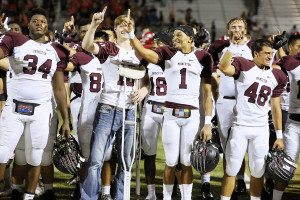Kade Massey (10) and Moonie Jackson (1) celebrate the victory during the singing of the school song.