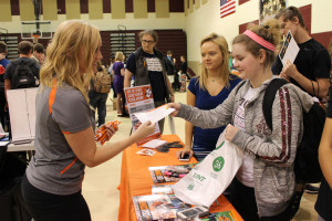 Students Allison Horn and Alexys Rock talk to college representatives.