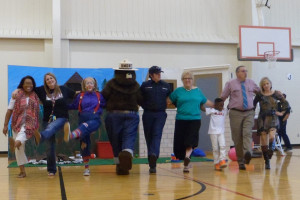 Godwin Elementary School teachers and administrators dance with Smokey Bear at the Fire Prevention presentation with the Princeton Fire Department.