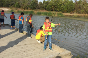 Cameron Rico proudly shows off a fish caught at the Collin County Adventure Camp during the fifth grade science camp excursion for Smith Elementary School.