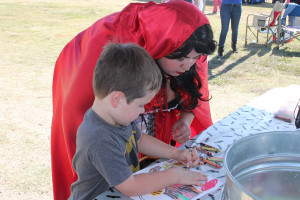 Walker colors a photo at the library booth's table alongside Little Red Riding Hood, Ann Marie Anderson.