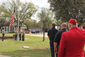 Residents pay their respect to the flag as it is raised during the Veterans Day ceremony Nov. 11 in Princeton.