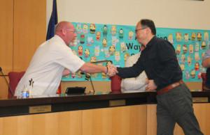 School board member Tim Tidwell shakes hands with Clark Junior High School Teacher of the Year Kuang-Jen Lu.