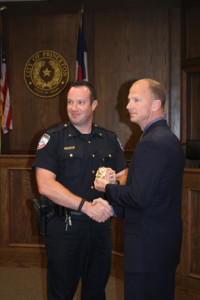 Police Chief James Waters hands over his badge temporarily to Assistant Police Chief Jerry Varner until another badge can be completed for the new position.