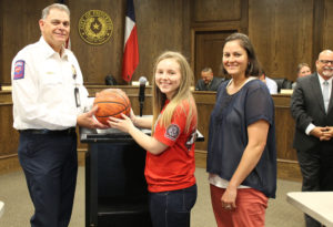 Princeton Fire Chief Tom Harvey accepts a signed basketball from Panthers varsity player Mackenzie Harper and girls' head coach Meaghan Hodapp. The basketball is from a fundraiser game between the girls' varsity team and city employees.
