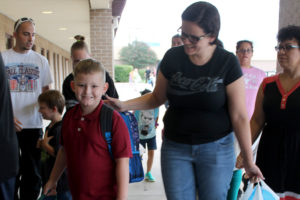 Braydin Burns is all smiles as he reports for the first day of classes at Lacy Elementary School with his mother, Samantha.
