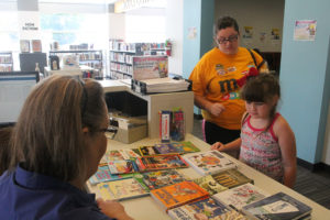 Cheyenne and her mom, Shannon Walker pick out a book with Librarian Cathy Dunkle at the ending program for the Summer Reading Club July 27.