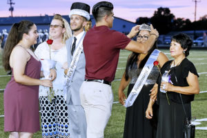 Last year's Homecoming King George Flores crowns 2016 Homecoming Queen Maggie Guapo while Homecoming King Hunter Peacher stands beside her along with their parents.