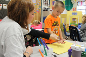 Mrs. Wilkins helps Bryson Johnson place a turkey-sized handprint on his Thanksgiving placemat at Godwin Elementary School. Students gave thanks for a variety of things on their placemats including family, siblings, pets and a lion.