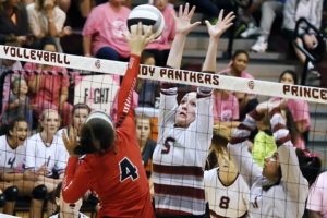 Shelbi Cook goes up for a block at the net as Sydney Bazan assists on the play